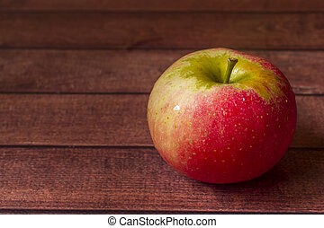 Fresh red apples with green leaves on a Dark wooden background.