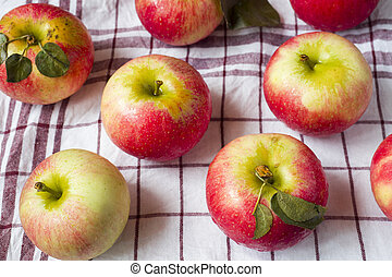 Fresh red apples with green leaves on a napkin. Dark wooden background.