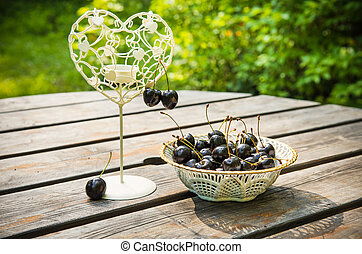 fresh red cherries berries in a white plate on the wooden table with candlestick in the shape of the heart outdoors in the garden