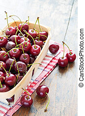Fresh red cherries in bowl on a wooden table