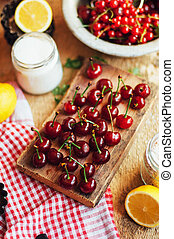Fresh red cherries on a rustic wooden table.