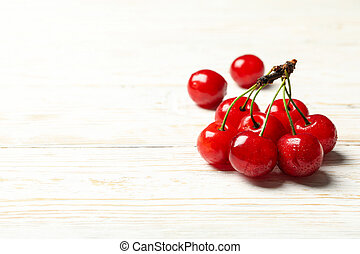 Fresh red cherry on white wooden background, close up