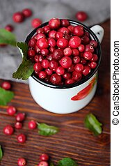Fresh red cranberries with leaves on the table