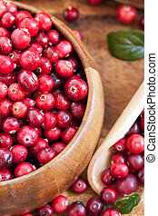 Fresh red cranberry in wooden bowl on the table