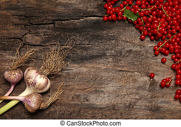 Fresh red currant berries and garlic on old wooden background