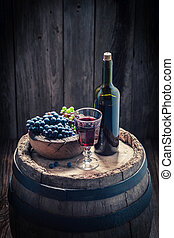 Fresh red grapes and wine on oak barrel