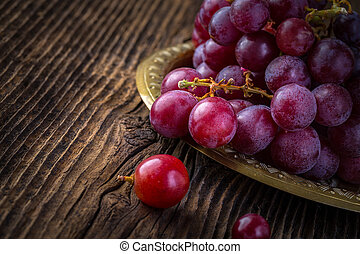 Fresh red grapes in old bowl on wooden table