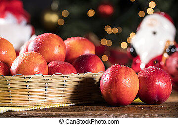 Fresh red nectarines in a wooden bowl.