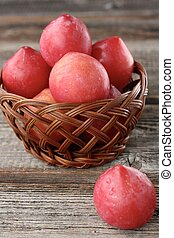 Fresh red plums on a wooden table