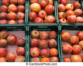 Fresh red pomegranate fruit in store containers.