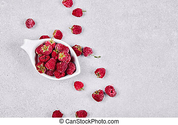 Fresh red raspberries in white bowl on white background. Top view