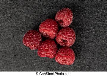 Fresh red raspberry on grey stone