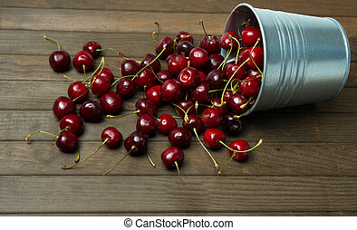 cherries in a small metal bucket overturned on the wooden table