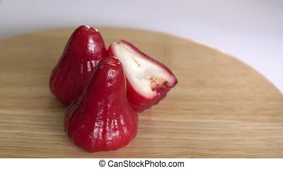 Fresh red rose apples rotate on wooden table