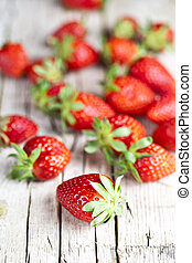 Fresh red strawberries on rustic wooden background.