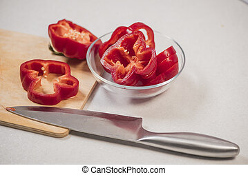 Fresh red sweet pepper on a wooden Board and in a glass bowl, near the knife