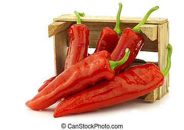 fresh red sweet peppers (capsicum) in a wooden crate on a white background