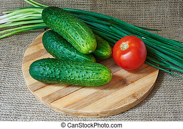 Fresh red tomatoes and cucumbers, green onions on a wooden tray