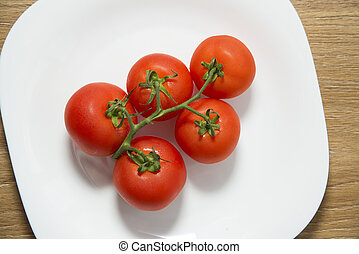 Fresh red tomatoes in white plate