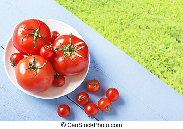 Fresh red tomatoes on wooden table in nature. Cherry tomatoes. Healthy food concept. Top view with copy space