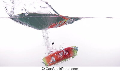 Fresh red watermelon slice falling into clear water with splash on white