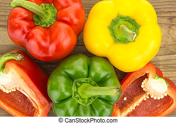 Fresh red,  yellow and green bell peppers, on wooden surface.