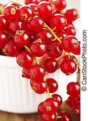 fresh redcurrants in bowl on wooden