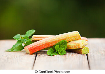 Fresh rhubarb with mint leaves on a wooden table