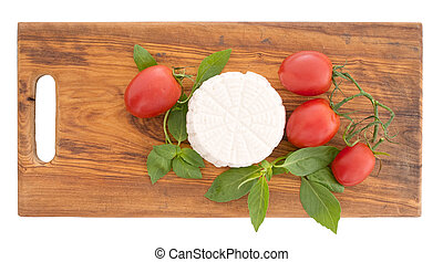 Fresh ricotta cheese with herb basil and tomatoes on rustic...