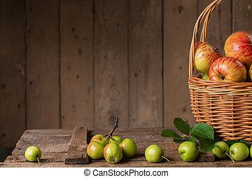 Fresh ripe apples in basket on vintage wood table