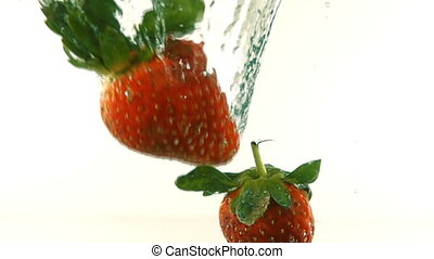fresh ripe berries and fruits fall into mineral water, slow...