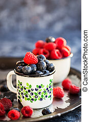 Fresh ripe blueberry and raspberry in mugs