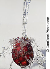 fresh ripe cherries falling into glass of water with bubbles on white background