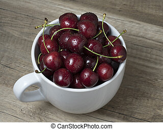 Fresh ripe cherries in a cup, on wooden background.