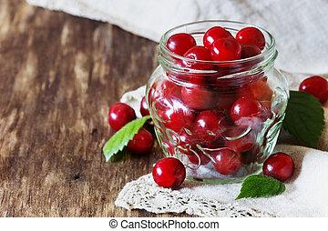 Fresh ripe cherries in a glass jar
