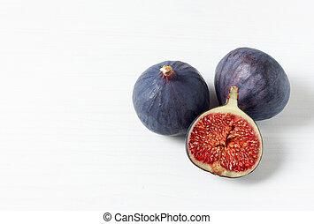 Fresh ripe figs on white background with space for text. Food Photo. Copy space. Purple figs with red seeds. Side view. Food concept