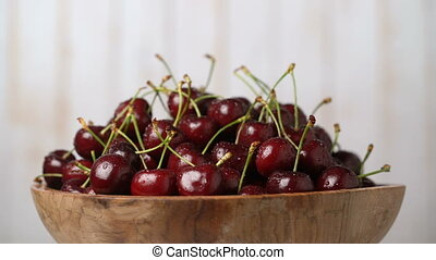 Fresh, ripe, juicy cherries in a wooden bowl, rotation seamless loopable. Food background. Gastronomy concept, organic food.