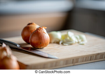 Fresh ripe onions on table in kitchen.