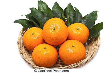 Fresh ripe orange fruits with leaves in a basket