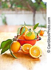 Fresh ripe oranges in a red sieve