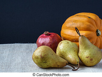 Fresh ripe organic Pears with pomegranate and pumpkin on table on sackcloth black backgroung.