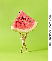 Miniature wooden human mannequin holds fresh ripe sweet watermelon's part on a lawn green background with soft shadows, copy space.