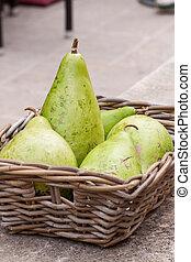 Fresh ripe pears in a wicker basket
