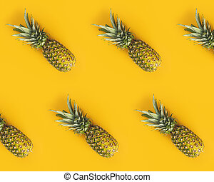 Fresh ripe pineapples on yellow background. Summer concept. ...