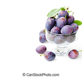 Fresh ripe plums in a glass bowl on white background