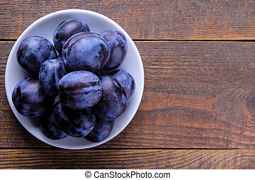 Fresh ripe plums in a plate on a brown wooden table. view from above. with place for inscription