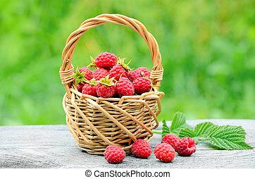 Fresh ripe raspberries in wicker basket