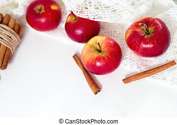 Fresh ripe red apples and cinnamon sticks on white wooden background