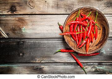 Fresh ripe red pepper in wooden bowl.