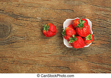 Fresh ripe strawberries in white bowl on wooden background.